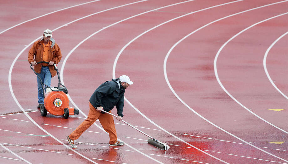 Workers attempt to dry the track during a weather delay in the afternoon session in the third and final day of the UIL state track and field championships at Mike Myers Stadium in Austin on Saturday, May 14, 2016.  MARVIN PFEIFFER/ mpfeiffer@express-news.net Photo: Marvin Pfeiffer, San Antonio Express-News / Express-News 2016