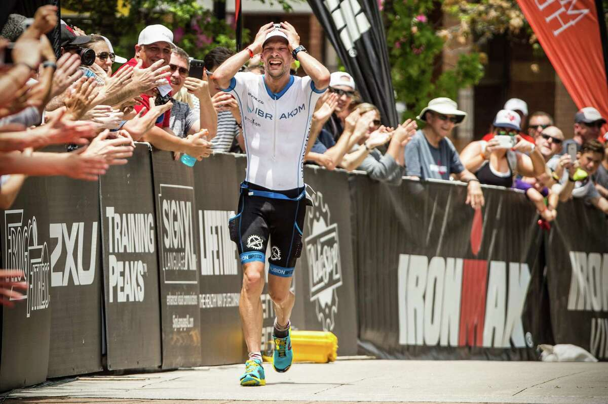 Patrick Lange, of Germany, reacts as he runs to the finish line to win the Memorial Hermann Ironman North American Championship Texas triathon on Saturday, May 14, 2016, in The Woodlands.