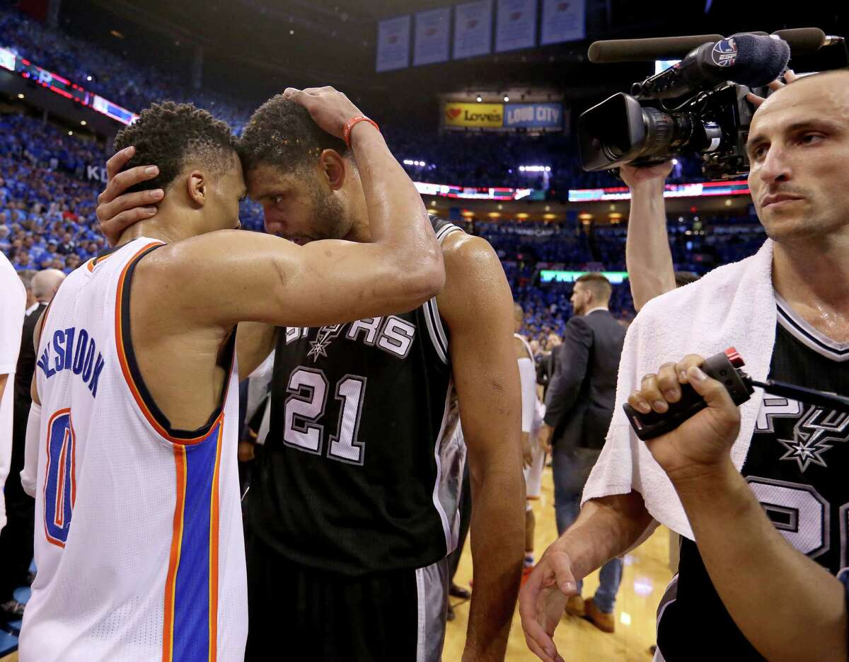 Oklahoma City Thunder's Russell Westbrook and San Antonio Spurs' Tim Duncan hug after Game 6 in the Western Conference semifinals as San Antonio Spurs' Manu Ginobili walks off the court Thursday May 12, 2016 at Chesapeake Energy Arena in Oklahoma City, Oklahoma. The Thunder won 113-99.