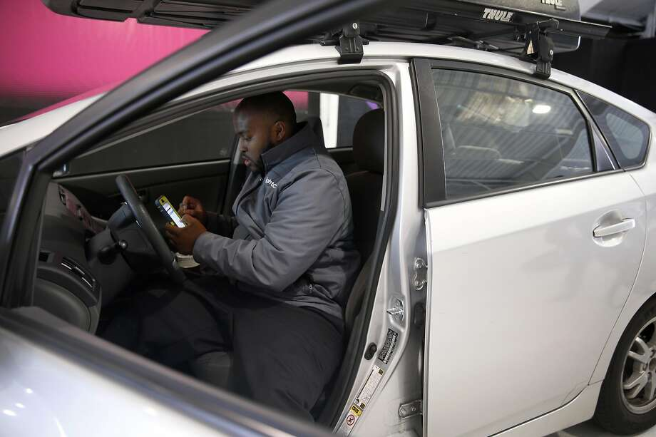 LaMarcus Harris records the mileage and condition of a client's car at FlightCar in South San Francisco. FlightCar offers free parking for airline travelers while they are out of town and rents those cars to others while the owners are away. Photo: Paul Chinn, The Chronicle