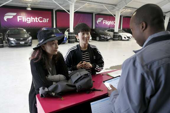 Ping Ye (left) and her daughter Lu Shan check in with Sam Saint-Jean before renting a car at FlightCar in South San Francisco, Calif. on Friday, May 13, 2016. FlightCar offers free parking for airline travelers while they are out of town and rents those cars to other arriving passengers while the owner is away in exchange.