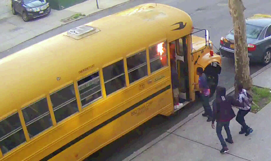 In this frame grab taken from surveillance video, children watch as pieces of cardboard they placed on a school bus begin to burn, Sunday, May 8, 2016, in the Crown Heights section of the Brooklyn borough of New York.  When the group of young, black children set fire to the school bus outside a Jewish school, it evoked bad memories of a violent riot in the same Brooklyn neighborhood 25 years ago. Relations between blacks and Jews in Crown Heights have been peaceful for many years, but some community leaders say tensions remain. (Beth Rifkah School via AP) ORG XMIT: NYRD403 / Beth Rivkah School