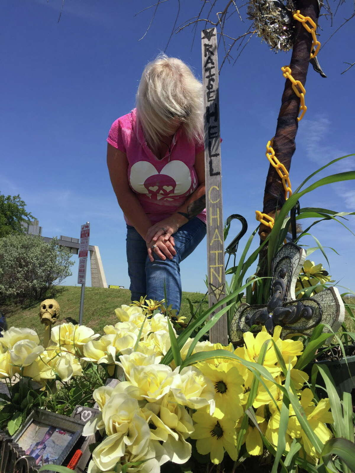 Yvonne Reeves leans over the shrine to seven members of the Cossacks Motorcycle Club, including her son, who were killed in May 2015 during a clash outside the Twin Peaks in Waco. Photo by Dane Schiller May 2016