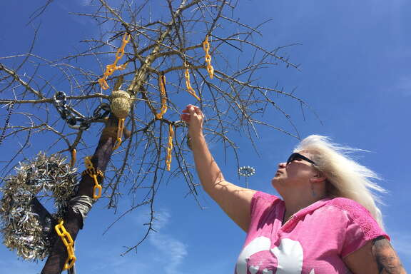 "Yvonne Reeves, whose son ""Chain"" was killed during the May 2015 biker clash at the Twin Peaks in Waco at a tree, beside the former sports bar, which rises from a shrine to seven members of the Cossacks Motorcycle Club who died that day.  By Dane Schiller, Houston Chronicle Photo taken in May 2016"