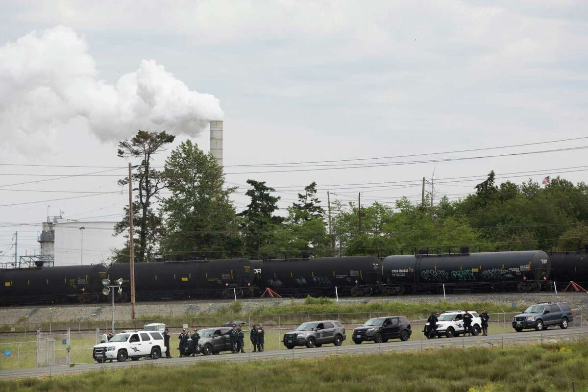Police guard oil cars in front of the Shell refinery on March Point during the Break Free PNW Indigenous Day of Action, Saturday, May 14, 2016. Shell is one major oil company that has not given to the $20 million fund with which Big Oil is fighting Initiative 1631.