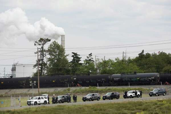 Police guard oil cars in front of the Shell refinery on March Point during the Break Free PNW Indigenous Day of Action, Saturday, May 14, 2016.