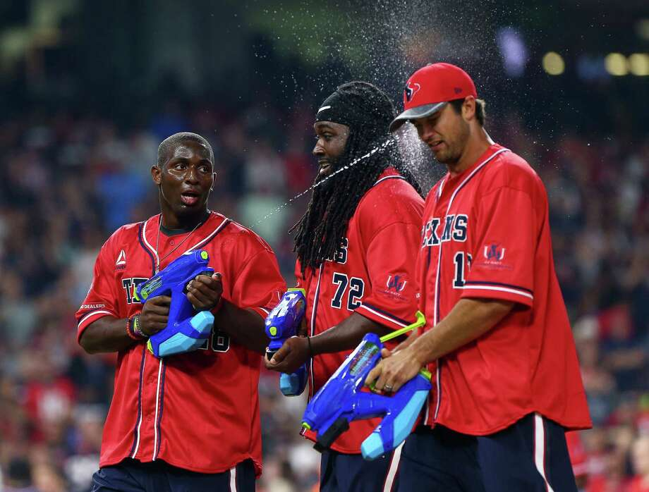 Houston Texans running back Alfred Blue (28) sprays quarterback Brock Osweiler in the face with a water gun during the third inning of the 4th annual J. J. Watt Charity Classic at Minute Maid Park Saturday, May 14, 2016, in Houston. Photo: Jon Shapley, Houston Chronicle / © 2015  Houston Chronicle