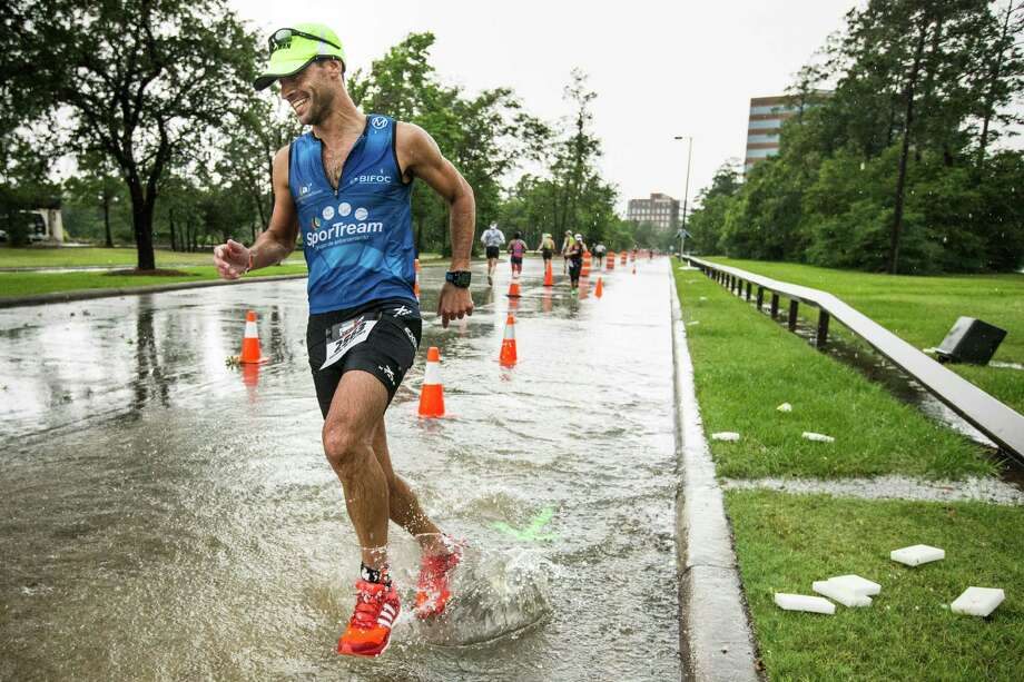 Ben Vinson turns a corner through a puddle of rainwater during the marathon leg of the Memorial Hermann Ironman North American Championship Texas triathon on Saturday, May 14, 2016, in The Woodlands. ( Brett Coomer / Houston Chronicle ) Photo: Brett Coomer, Staff / © 2016 Houston Chronicle