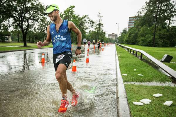 Ben Vinson turns a corner through a puddle of rainwater during the marathon leg of the Memorial Hermann Ironman North American Championship Texas triathon on Saturday, May 14, 2016, in The Woodlands. ( Brett Coomer / Houston Chronicle )