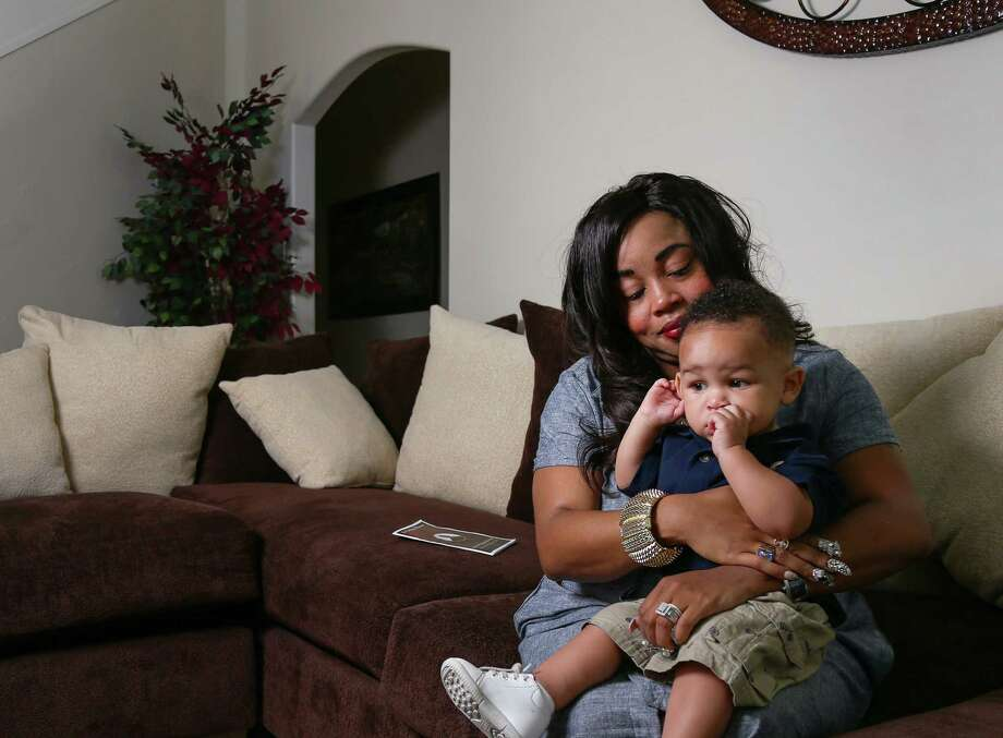Candice Hinton, holding her son, Rodrin Jr., said an investigator assigned to her husband's death has only given her a 'very vague' account of what happened at the Harris County Jail.