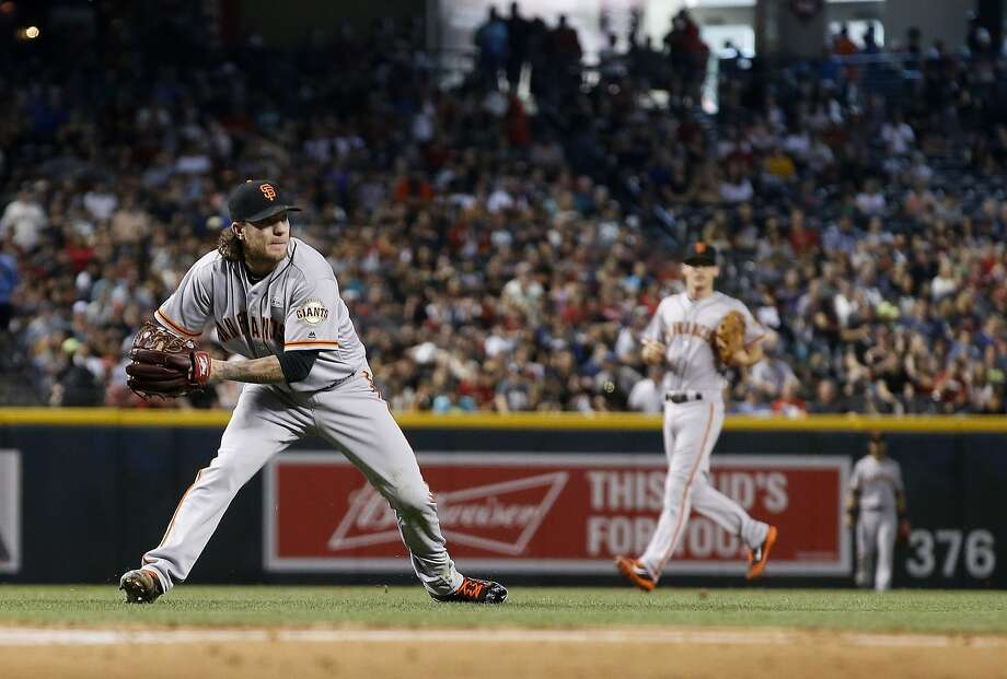 After fielding a grounder, San Francisco Giants' Jake Peavy, left, gets set to throw to first base to get Arizona Diamondbacks' Paul Goldschmidt out as Kelby Tomlinson, right, looks on during the first inning of a baseball game Saturday, May 14, 2016, in Phoenix. (AP Photo/Ross D. Franklin) Photo: Ross D. Franklin, Associated Press