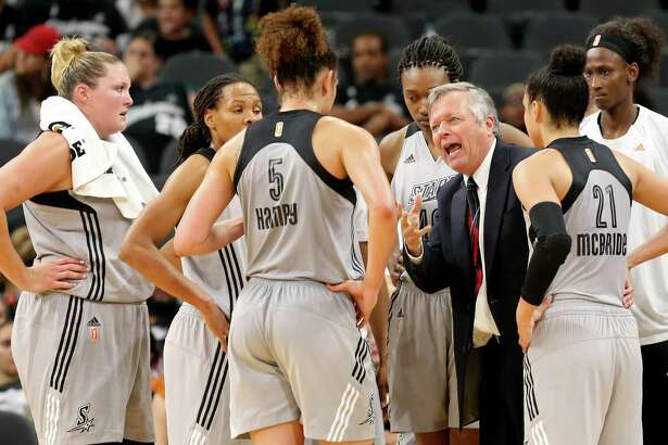 San Antonio Stars head coach Dan Hughes (center) huddles with the team during a timeout in second half action against the Atlanta Dream on May 14, 2016 at the AT&T Center.