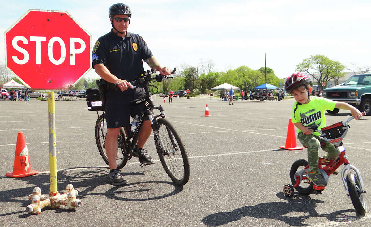 Police Sgt. Matt Riendeau guides Parker Lopez, 4, of Fairfield, around a course at Fairfield PAL's Bicycle Rodeo in the Jennings Beach parking lot Saturday morning.