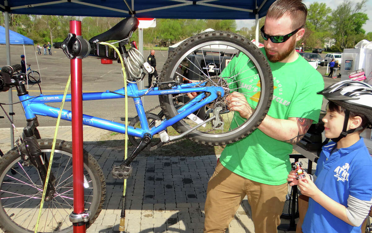 Aydan Gibson, 9, of Fairfield, stands by as Tom Naughton of Zane's Cycles gives his bike a tune-up at Fairfield PAL's Bicycle Rodeo.