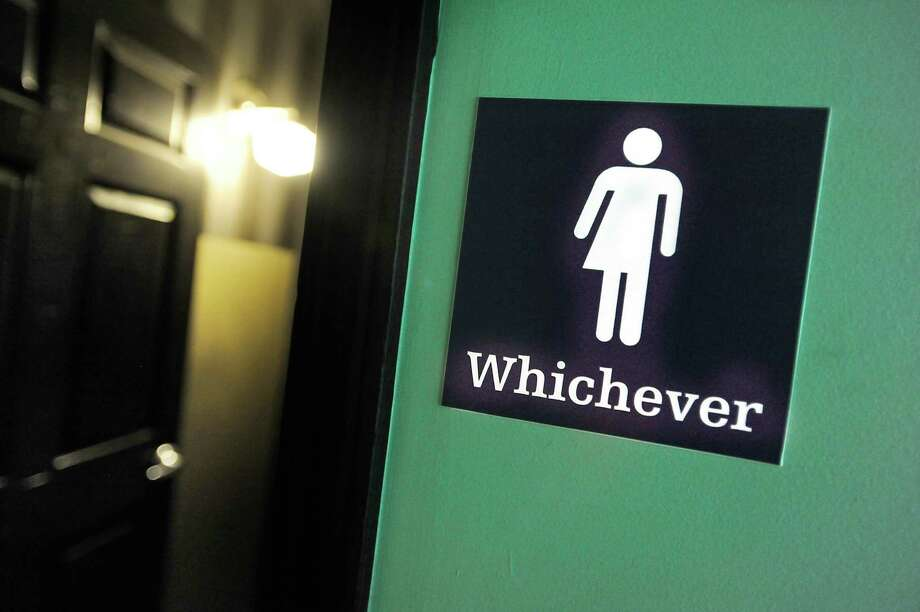 A gender neutral sign is posted outside a bathrooms at Oval Park Grill in Durham, N.C. Photo: Sara D. Davis / Getty Images / 2016 Getty Images