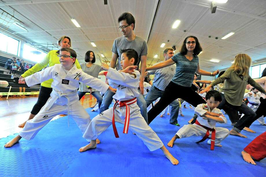 From left, James Kolman, 8, Jashan Wu, 5, and Alex Bowbeer, 7, all of Stamford, perform a set of warm up exercises with their parents during the YB World Taekwondo Academy championship tournament at Rippowam Middle School in Stamford on May 14, 2016. Photo: Matthew Brown / Hearst Connecticut Media / Stamford Advocate