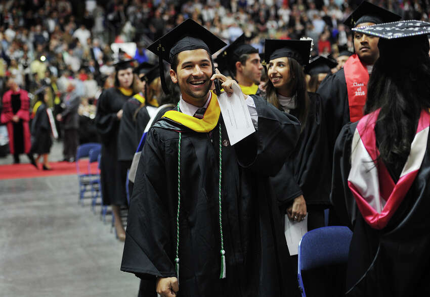 Grad John Varsam, of Queens, NY, takes a call after marching in to Sacred Heart University's graduation at the Webster Bank Arena in Bridgeport, Conn. on Sunday, May 15, 2016.