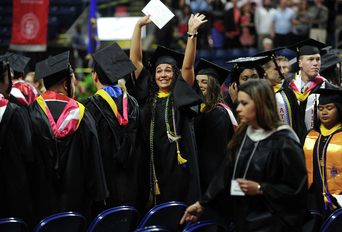 Grad Amand Forlenza, of Caldwell, NJ, waves excitedly to her family after marching in to Sacred Heart University's graduation at the Webster Bank Arena in Bridgeport, Conn. on Sunday, May 15, 2016.