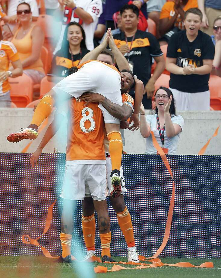 Houston Dynamo forward Erick Torres (9) jumps onto Giles Barnes (10) and Cristian Maidana (8) after Barnes scored a goal during the second half of an MLB soccer game at BBVA Compass Stadium, Sunday, May 15, 2016, in Houston.  Dynamo won the game 1-0. Photo: Karen Warren, Houston Chronicle / © 2016 Houston Chronicle