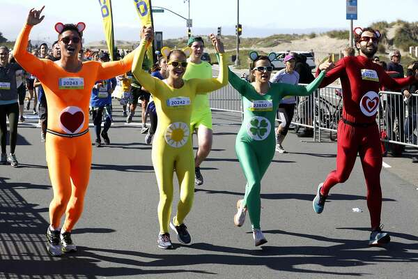 A group dressed as Care Bears celebrate as they near the Bay to Breakers finish line at Ocean Beach in San Francisco, California, on Sunday, May 15, 2016.