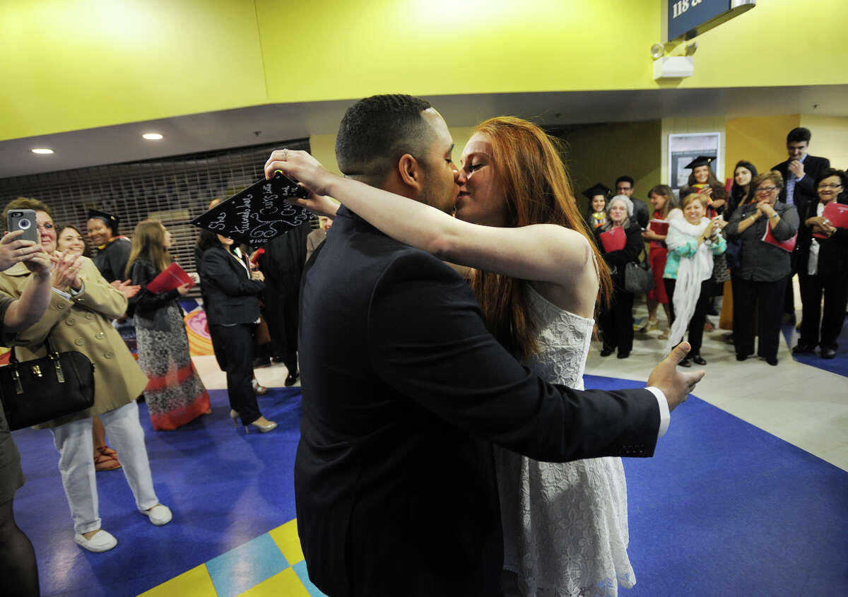 Sealed with a kiss, Erin Civitelli, of Stratford, accepts a marraige proposal from her boyfriend, Josh Tong, of North Haven, immediately following her graduation from Sacred Heart Universuity at the Webster Bank Arena in Bridgeport, Conn. on Sunday, May 16, 2016.