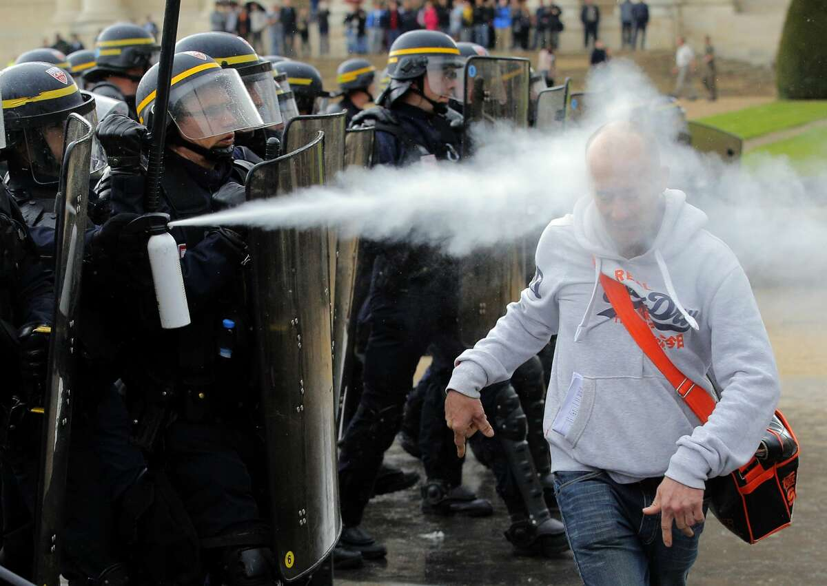 French riot police officers sprays pepper gas at a demonstrator during a protest against Labor Law as the Socialist government decided to force the bill through Parliament without a vote, in Paris, Thursday, May 12, 2016. France's government is facing a major test as lawmakers hold a no-confidence vote, prompted by a deeply divisive labor law allowing longer workdays and easier layoffs. (AP Photo/Christophe Ena)
