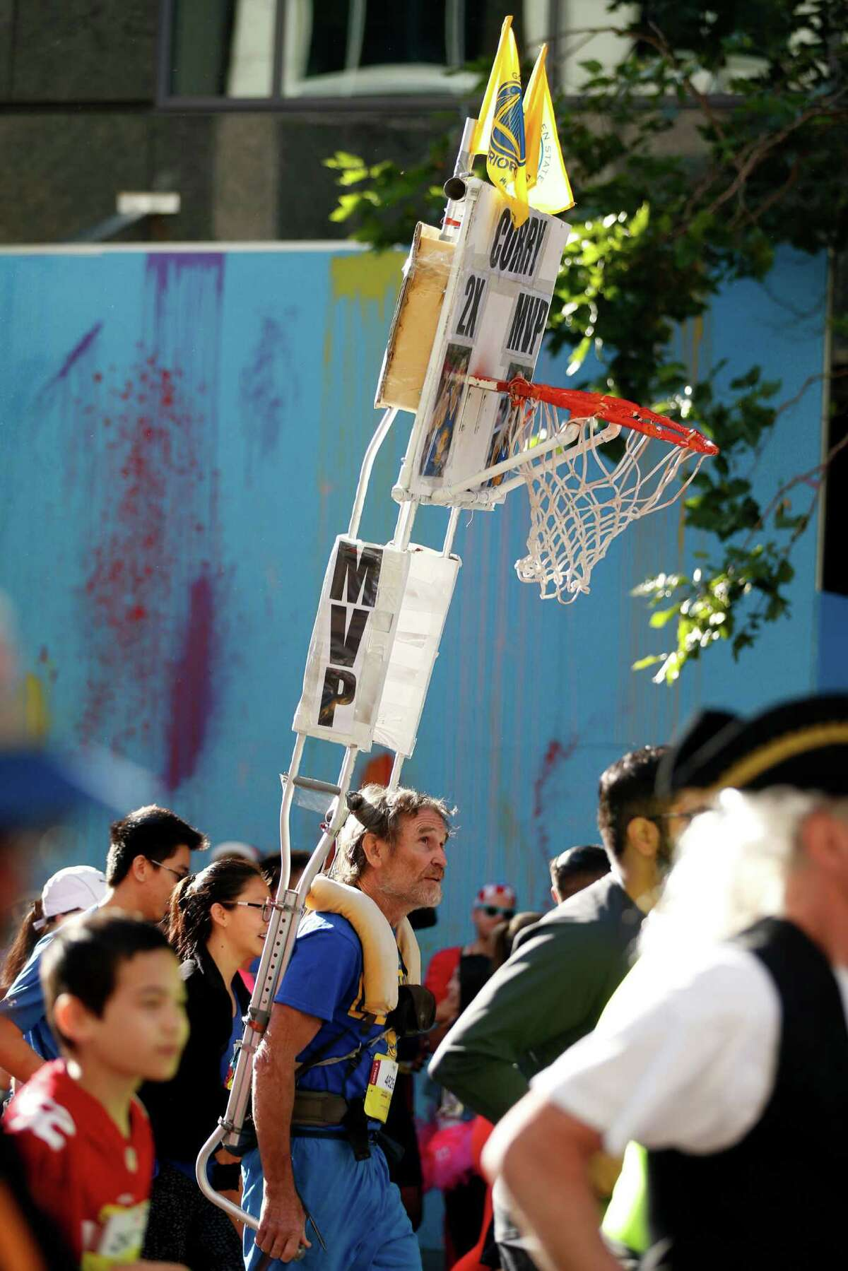 A Bay to Breakers' participant runs with a basketball hoop to salute Stephen Curry's back to back MVP awards in San Francisco, Calif., on Sunday, May 15, 2016.