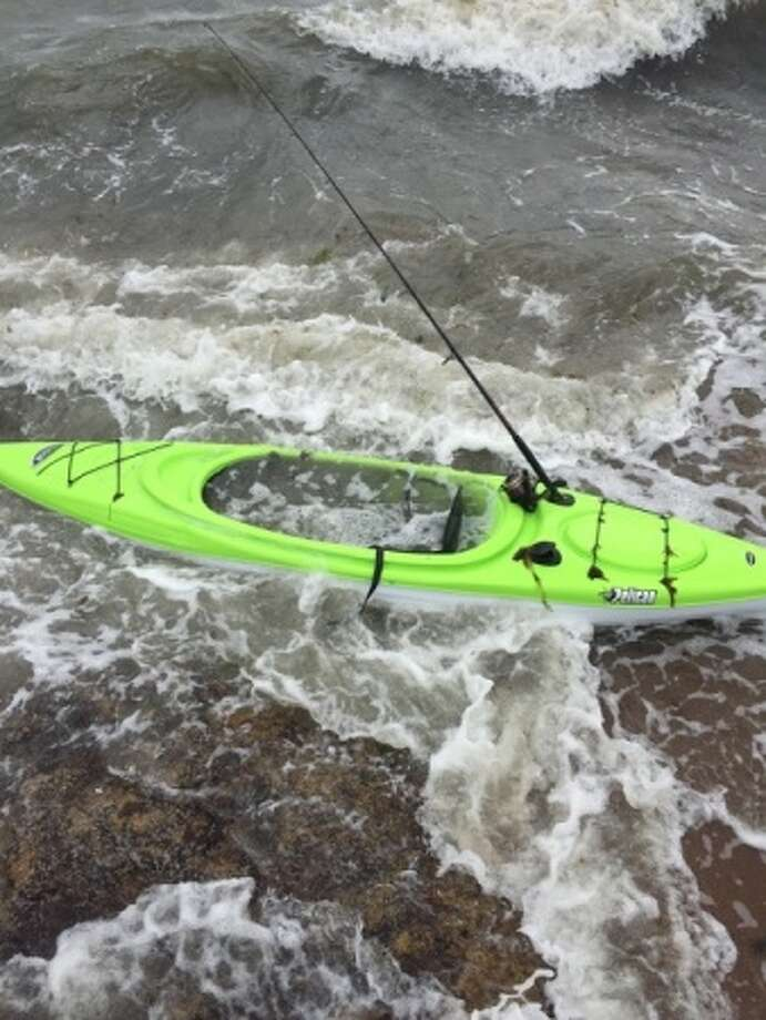 Crews from the Coast Guard and local agencies are searching for a possible missing person after this unmanned, bright green kayak was found near the rocks at Lighthouse Point Sunday. Photo: Contributed / Contributed