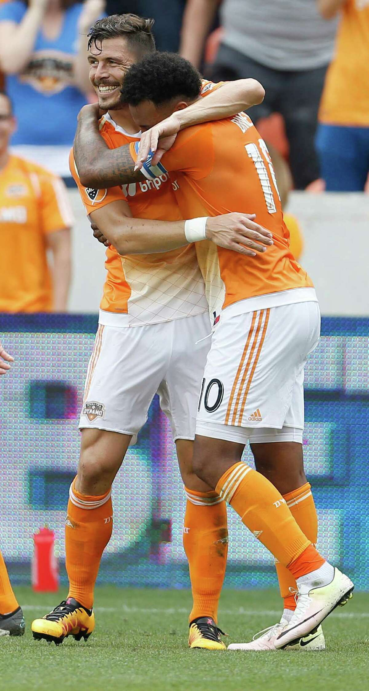 Houston Dynamo defender Agus (4) hugs Dynamo forward Giles Barnes (10) after Barnes scored a goal during the second half of an MLB soccer game at BBVA Compass Stadium, Sunday, May 15, 2016, in Houston. Dynamo won the game 1-0.