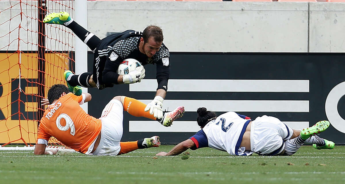 Real Salt Lake goalkeeper Jeff Attinella (24) flies over Dynamo forward Erick Torres (9) and Real Salt Lake defender Tony Beltran (2) during the first half of an MLB soccer game at BBVA Compass Stadium, Sunday, May 15, 2016, in Houston.