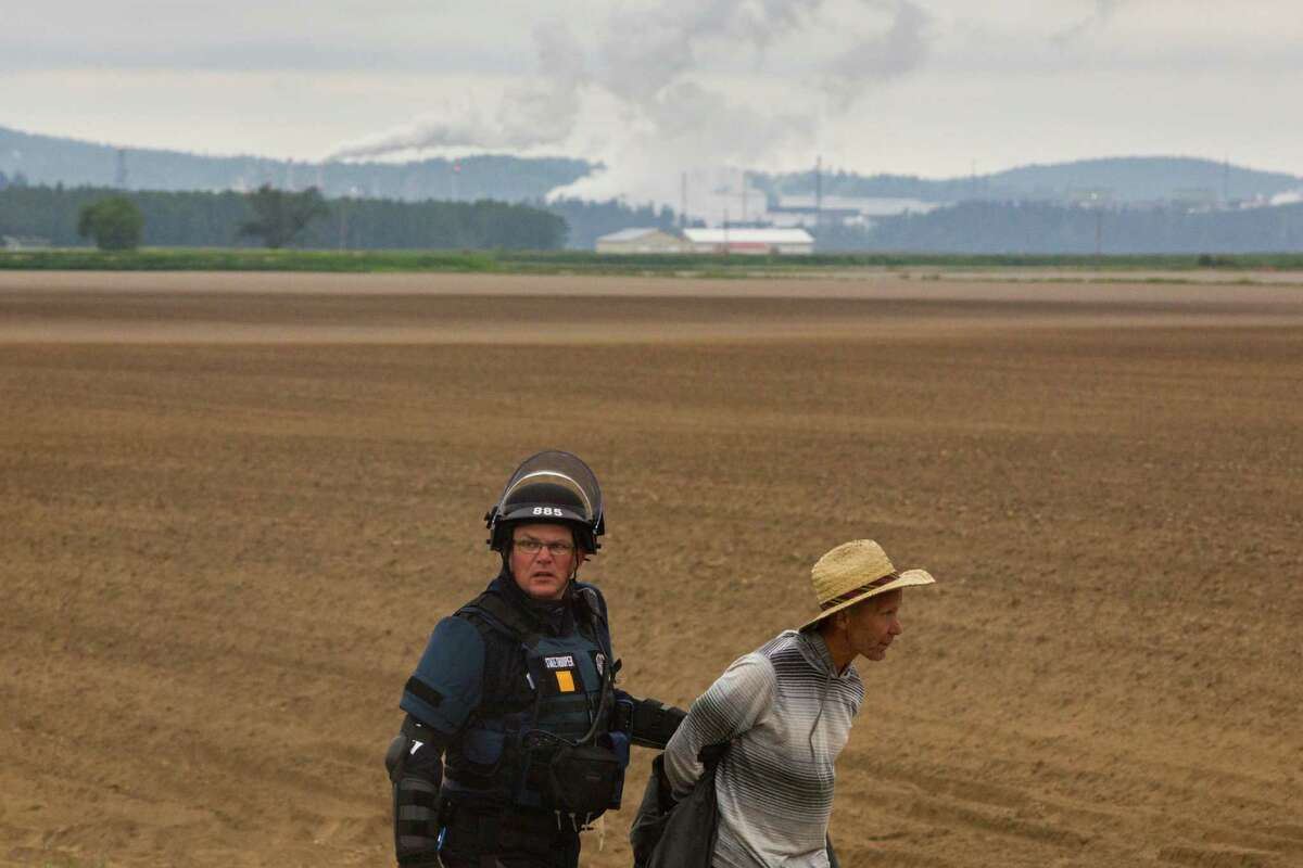 A Washington State Patrol officer arrests an environmentalist who remained at the oil train track blockade after authorities attempted breaking the group up, in Anacortes on Sunday, May 15, 2016. The interaction between parties was cordial and non-violent.