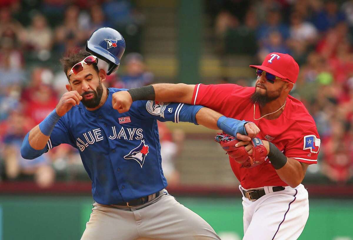 Toronto's Jose Bautista catches a right hook from Rangers second baseman Rougned Odor after the outfielder's late slide trying to break up a double play. Both players were among the eight ejections in Texas' 7-6 win Sunday in Arlington.