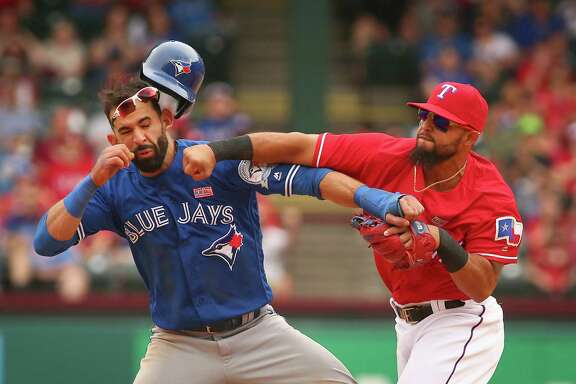 Toronto's Jose Bautista catches a right hook from Rangers second baseman Rougned Odor after the outfielder's late slide trying to break up a double play. Both players were among the eight ejections in Texas' 7-6 win.