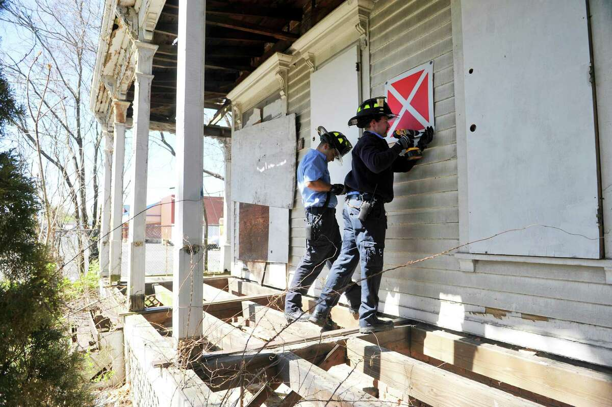 Troy firefighter Chris Agars, left, and Justin Miter stand on a porch missing boards to attach a red sign with a white X on it to the front of the building at 867 2nd Ave. on Thursday, April 28, 2016, in Troy, N.Y. The sign signifies to firefighters that the building is unsafe to enter. (Paul Buckowski / Times Union)