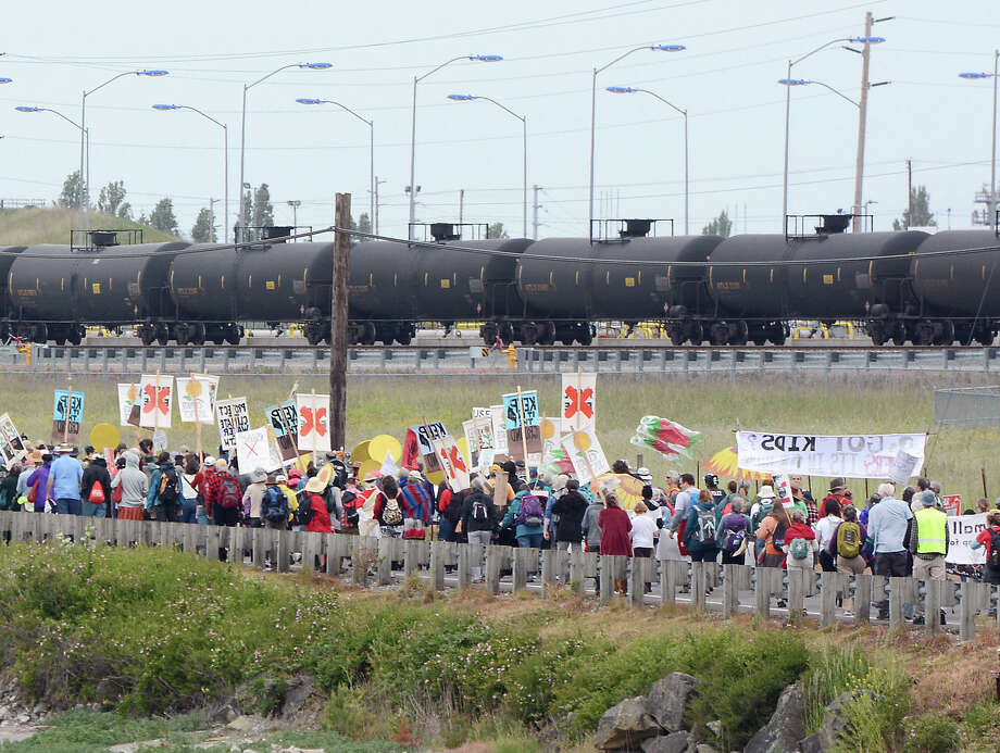 "Anti-oil protestors walk past the Tesoro refinery rail yard in Anacortes, Wash., on Saturday, May 14, 2016. The protests are part of a series of global actions calling on people to ""break free"" from dependence on fossil fuels. (Scott Terrell/Skagit Valley Herald via AP) Photo: Scott Terrell, MBR / Associated Press / Skagit Valley Herald"