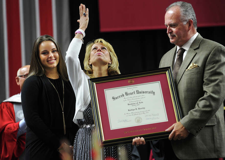 Darla Doorhy blows a kiss to her daughter, Kaitlyn, in heaven as she and husband Joe Doorhy, of Mattatuck, N.Y., receive a diploma in her honor during Sacred Heart University's graduation at the Webster Bank Arena in Bridgeport on Sunday. Kaitlyn Doorhy died after being hit by a car while a student at the school. Sister Carly Doorhy, left, plans to attend the university as an incoming freshman this fall. For an online slideshow, go to http://bit.ly/1rNRPJq Photo: Brian A. Pounds / Hearst Connecticut Media / Connecticut Post