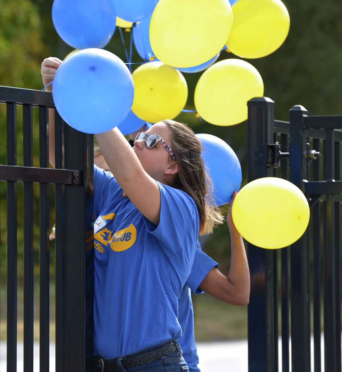 Leah Thompson, 15, ties blue and yellow balloons on the fence by the entrance to the Town Park Beach for Brookfield's celebration to mark the completion of the Town Park Beach on Candlewood Lake, on Saturday, September 26, 2015, in Brookfield, Conn. Thompson is a 10th grader at Brookfield High School and a member of the Key Club International who's members were volunteering at the celebration.