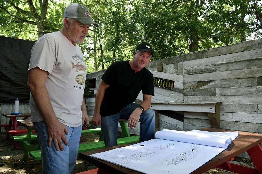 Scott Moore, left, the founder and owner of Tejas Chocolate Craftory on N. Elm St. in downtown Tomball, visits on his patio dining area with Bryan Hutson, a local attorney and developer who is working to transform Old Town Tomball. (Photo by Jerry Baker/Freelance) Photo: Jerry Baker, Freelance