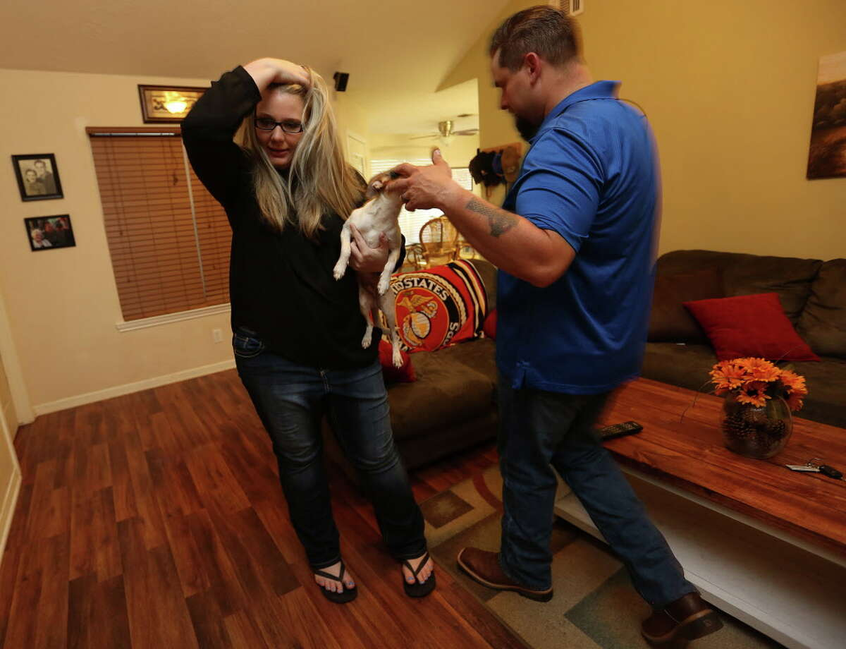 Morgan English holds onto Max, as her husband, William, walks by in their Brenham, Texas home on Tuesday, May 3, 2016. The two, who were arrested following a shoot-out in Waco, Texas, are expecting their first child.