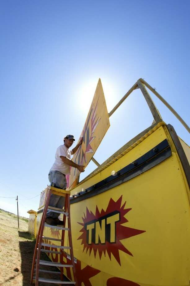 Jeff Kelly hangs a nameplate on top of the TNT Fireworks stand at CR 1140 and E. Loop 250 Saturday morning.   Kelly, who works for the company America Promotional Events out of Lubbock which runs the local TNT stands, said he had a total of six locations to ready for fireworks sales Saturday. photo by Gary Rhodes