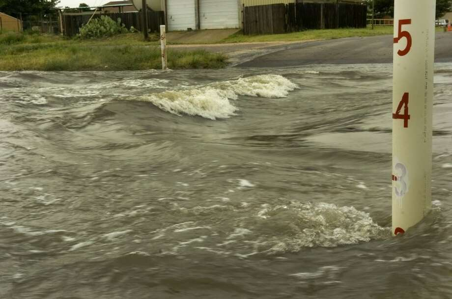 Flood waters still form waves as they rush down the draw Wednesday moring crossing Benton Street. Photo by Tim Fischer/Midland Reporter-Telegram