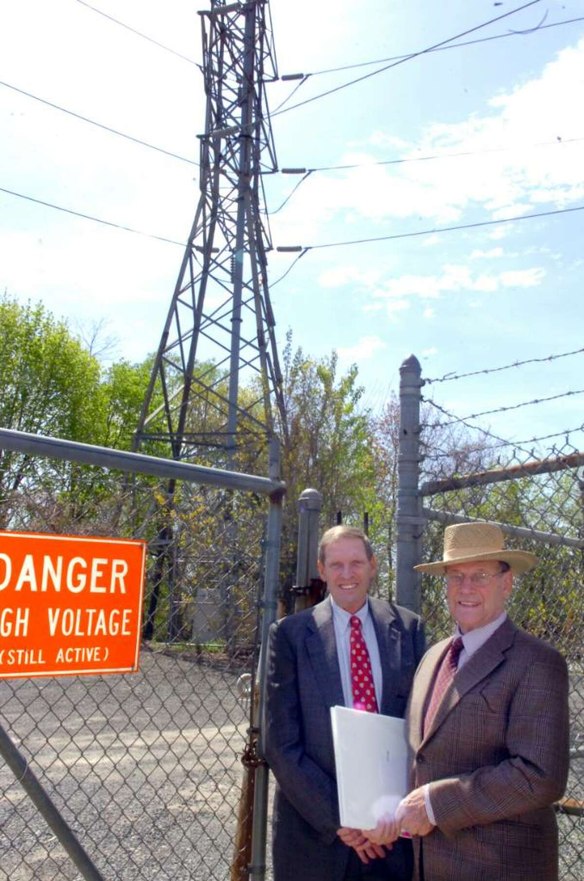Attorney Dean Montgomery, left, and his brother Barry stand near one of three cell phone towers at the site of the former Cos Cob power plant on Thursday, April 15, 2010. Barry Montgomery has launched a lawsuit against the town on its plans to proceed to put a park on the site.