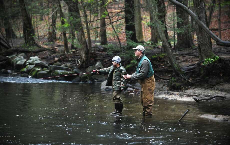 Stephen Getlik holds onto his son Tyler Getlik, 8, as they fish on opening day of the season at the Mianus River Trout Management Area in Stamford, Conn. on Saturday April 17, 2010. Photo: Kathleen O'Rourke / Stamford Advocate