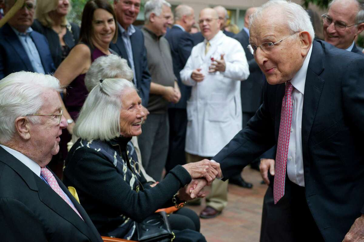 Carl Bennett, right, shakes hands with Grace and Dan Tully during a ceremony to recognize the Carl and Dorothy Bennett Foundation, which made a $9.1 million gift to Stamford Hospital and made Carl Bennett the largest Stamford Hospital donor, at the Bennett Cancer Center on Wednesday, September 24, 2014.