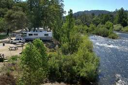 RV's are backed into their camp site spaces on the American River at Coloma Resort in Coloma, Calif., on Monday, June 27, 2005. Photo by Steve Yeater/For The Chronicle Ran on: 06-30-2005 Coloma Resort is a kid-friendly place, with small wading beaches, a swimming pool and gold flumes for panning displays. Ran on: 06-30-2005 Ran on: 06-30-2005