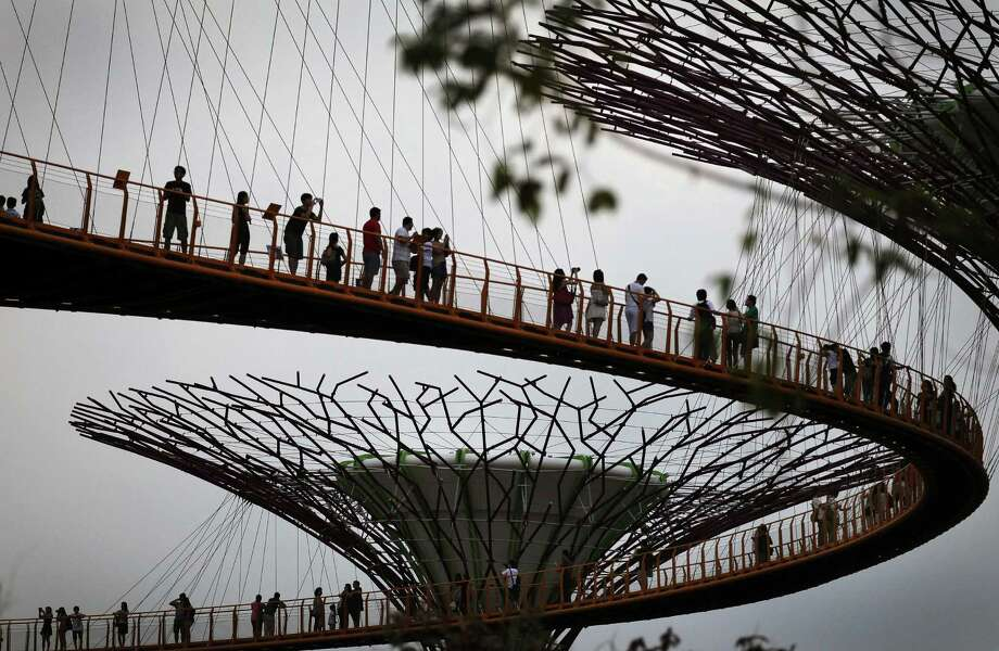 FILE - In this Aug. 18, 2012 file photo, silhouettes of people line the sky as they stand on a skyway suspension bridge through a Supertree grove at the Gardens by the Bay in Singapore. Travelers often use Singapore as a quick stopover on long flights but there are plenty of attractions here to justify a visit of several days. (AP Photo/Wong Maye-E, File) Photo: Wong Maye-E, STF / Copyright 2016 The Associated Press. All rights reserved. This material may not be published, broadcast, rewritten or redistribu