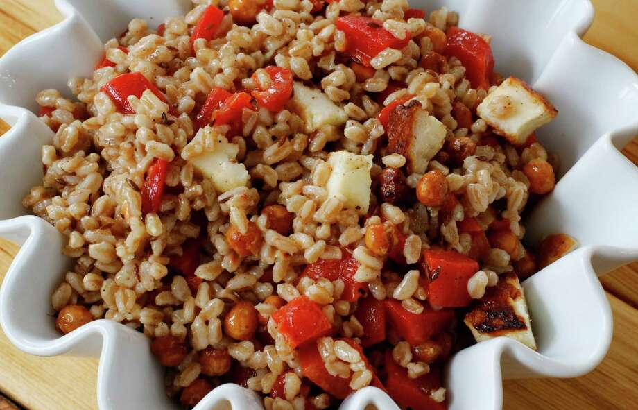 This salad combines savory roasted chickpeas with grill hallmoumi cheese and nutty cooked farro for a light, but hearty spring salad. Photo: J.M. Hirsch, STF / AP