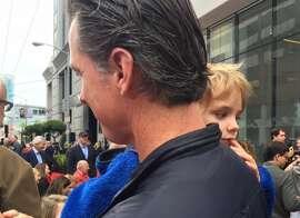 Gavin Newsom holds son Hunter at SFMOMA opening.
