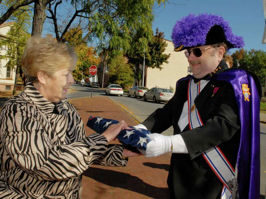 Marion Field, left, of Troy Little Italy accepts a folded American flag from Ron Hulin, commander of the Knights of Columbus Assembly 702 and a member of the Fourth Degree, at a Columbus Day Memorial Service at Troy's Columbus Square, Monday, Oct. 12, 2009.   (Luanne M. Ferris / Times Union) Photo: LUANNE M. FERRIS / 00005887A