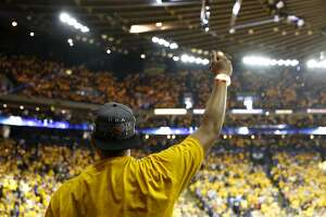 A fan raises his arm in celebration during the first game of the Western Conference Finals between the Warriors and the Oklahoma City Thunder at Oracle Arena in Oakland, California, on Monday, May 16, 2016.